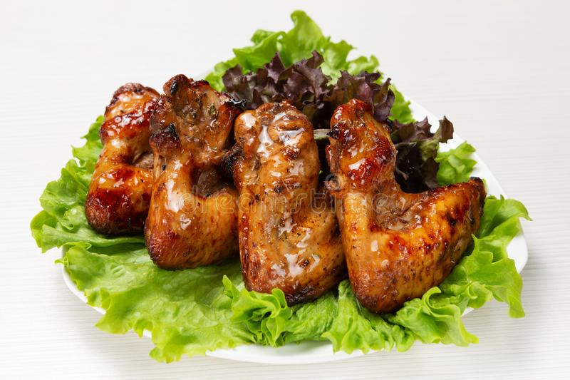 Fried chicken wings with a plate, on a lettuce leaf, in sweet sauce royalty free stock image