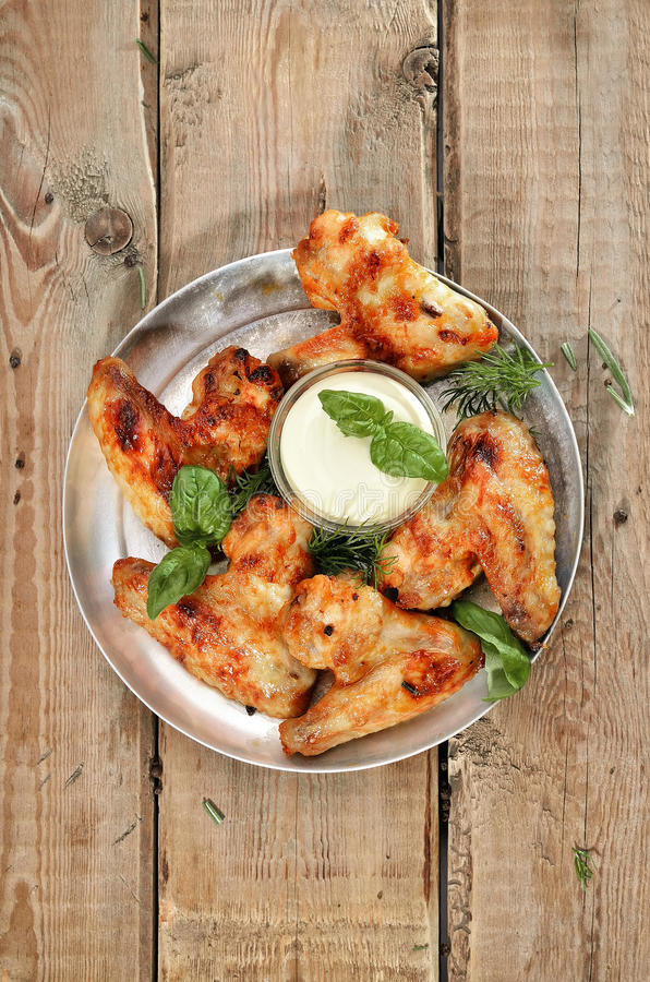 Fried chicken wings with sauce on rustic table stock images