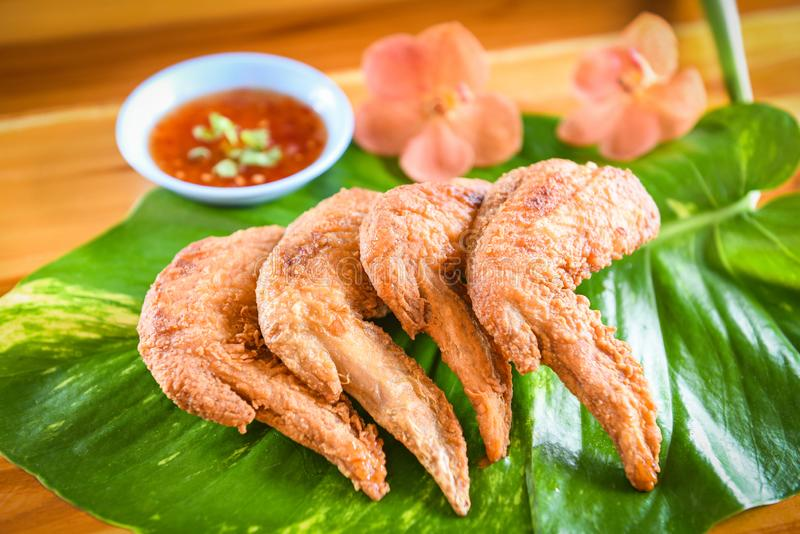 Fried chicken wings served on leaves with sauce top view - crispy chicken wings on wooden table , Thai Food Asian stock photo