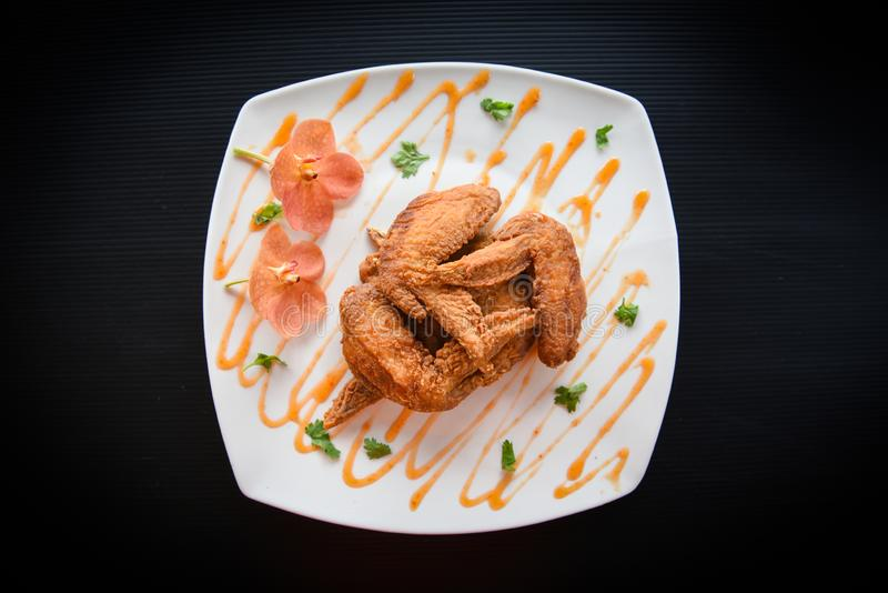Fried chicken wings served on plate with sauce top view - plate of crispy chicken wings on black background , Thai Food Asian stock image
