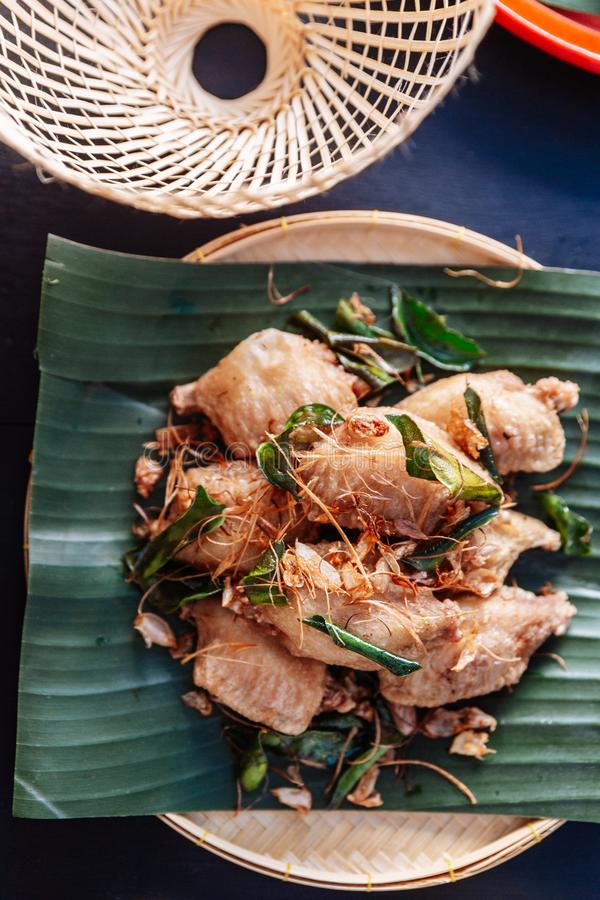 Fried chicken wings in Thai northeastern style with garlic and kaffir lime leaves served on banana leaf royalty free stock images