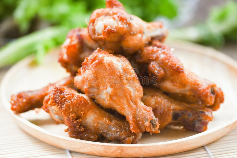 Fried chicken wings on wooden plate - Baked chicken wings BBQ stock photo