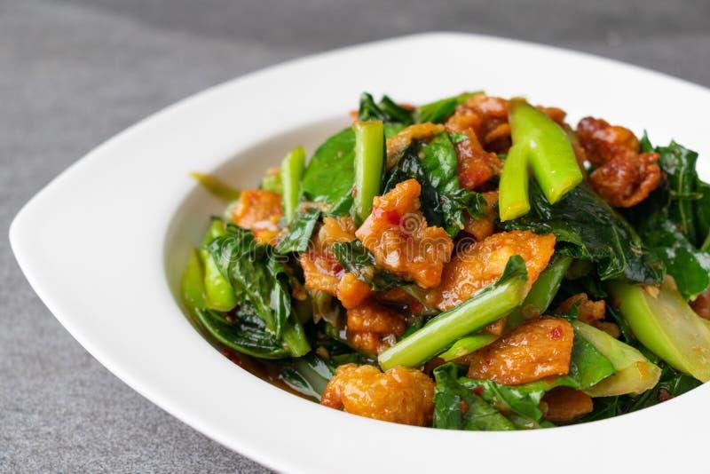 Fried Chinese gr?nk?l med frasig hudh?na i ostrons?s och chili i den vita matr?tten arkivbild