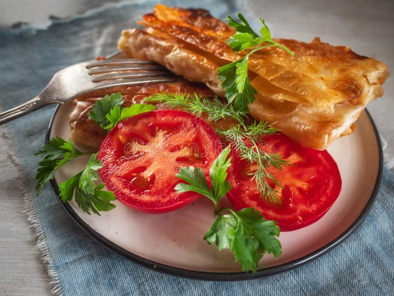 Fried closed sandwich with vegetables on a round plate, close-up royalty free stock photo