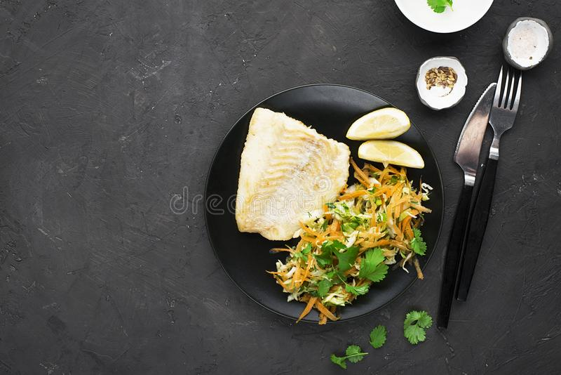 Fried cod with salad from fresh carrots, cabbage, cucumber and dill. Top view. Horizontal. stock photo