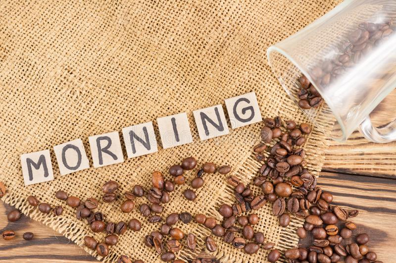 Fried coffee beans poured out of glass on hessian sack cloth beside handwritten word MORNING laid out of square cardboard piece. Fried coffee beans on hessian royalty free stock photography
