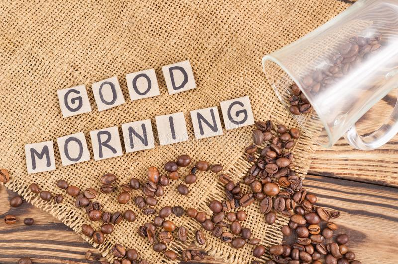 Fried coffee beans poured out of glass on hessian sack cloth beside handwritten words GOOD MORNING laid out of square cardboard pi stock photos