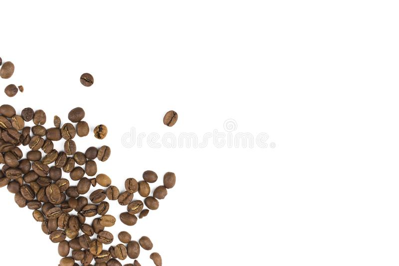 Fried coffee beans isolate in the lower left corner, copy space royalty free stock images