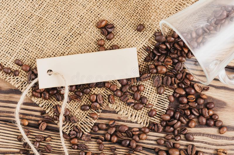 Fried coffee beans poured out of glass beside rectangle blank paper with rope on hessian sack cloth royalty free stock photo