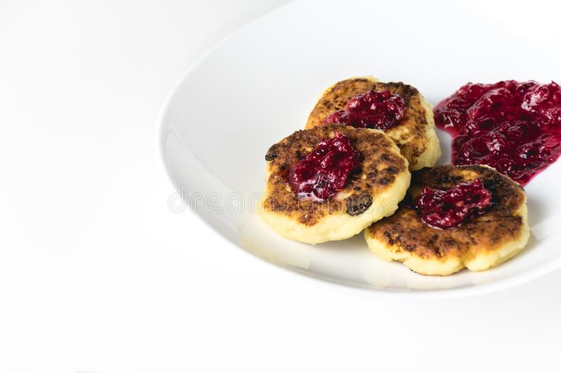 Fried cottage cheese pancakes on a white plate. Syrniki with red jam on top royalty free stock image