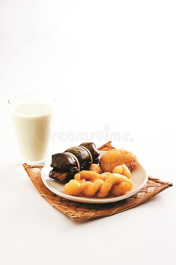Fried crispy baked asian cake with glass of milk on white background stock photography
