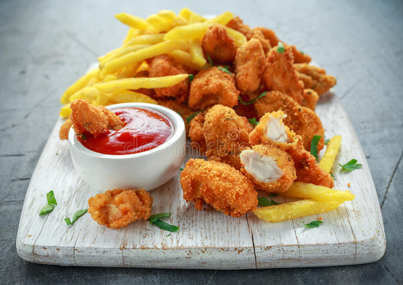 Fried crispy chicken nuggets with french fries and ketchup on white board royalty free stock image
