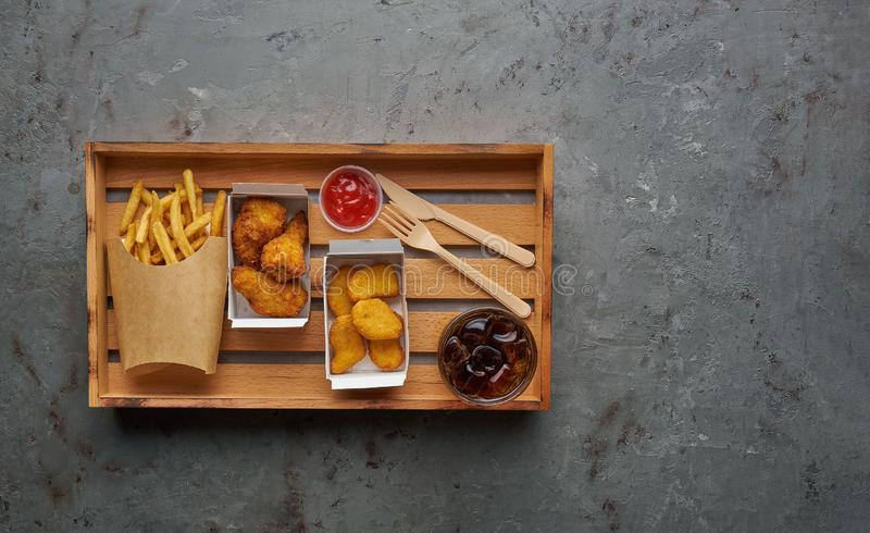 Fried crispy chicken nuggets with legs, ketchup, french fries and cola on wooden tray, top view, copy space. royalty free stock photos