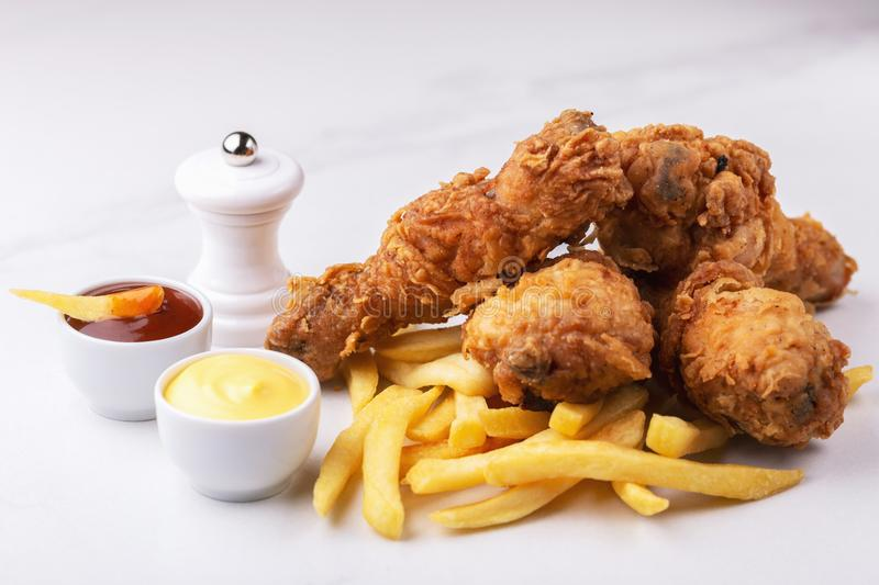 Crispy chicken legs and french fries potatoes. Fast junk food. Fried crispy and spicy chicken legs and french fries potatoes with sauces. Fast and junk food stock image