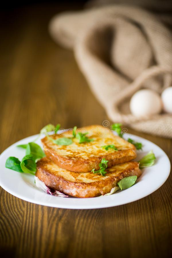 Fried croutons in eggs with greens in a plate. On a wooden table stock photography