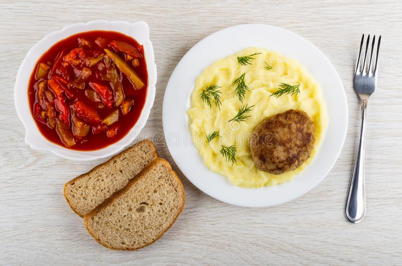 Fried cutlet with mashed potato, dill in plate, bread, bowl with lecho, fork on table. Top view stock images