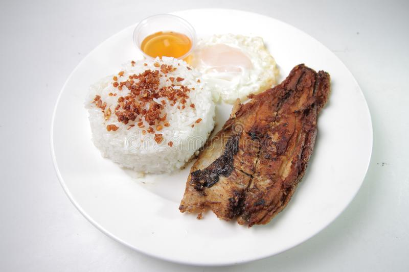 Fried Daing na Bangus med vitlök Fried Rice, Fried Egg och inlagd Papaya Daing Silog arkivbild