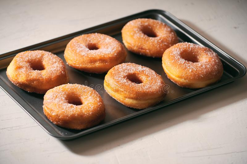 Fried Donuts with Powdered Sugar on metal baking dish royalty free stock photo