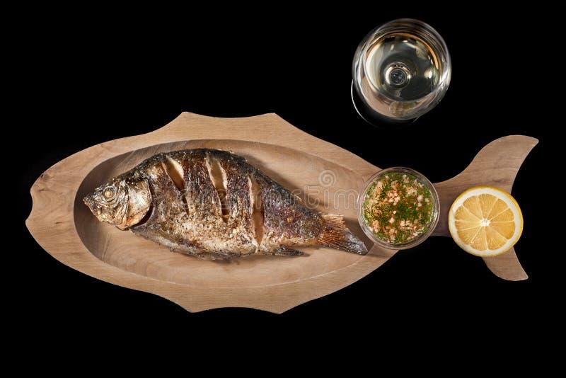 Fried Dorado fisk med citronen och ett exponeringsglas av vitt vin på en svart bakgrund kopiera avstånd royaltyfria foton