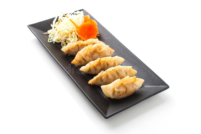 Fried Dumpling aisló en la placa negra en el fondo blanco, Gyoz imagen de archivo