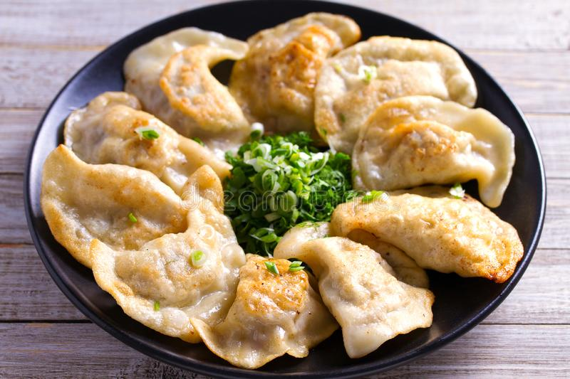 Fried dumplings stuffed with meat and served with chopped parsley and spring onion on a black plate on a wooden rustic table. stock images