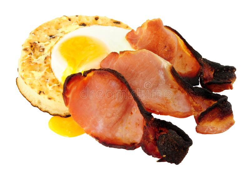 Fried Egg And Bacon Rashers sur un grand crumpet anglais photo stock