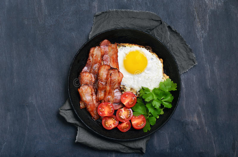 Fried egg. With bacon, tomatoes and parsley in frying pan on dark background, top view stock image