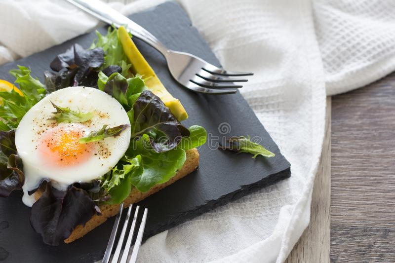Fried eggs with bread toast. On lettuce in a black plate stock images