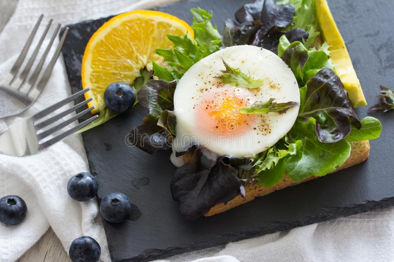Fried eggs with bread toast. On lettuce in a black plate royalty free stock photo