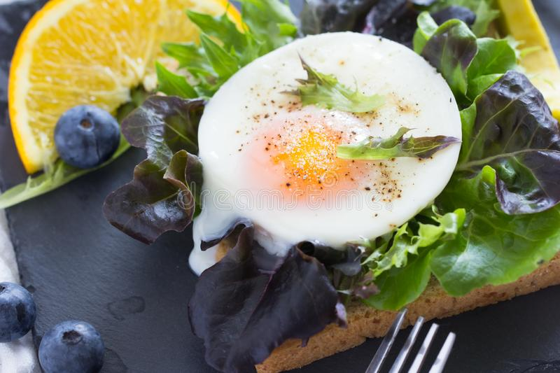 Fried eggs with bread toast. On lettuce in a black plate royalty free stock photos