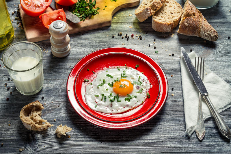 Fried egg for breakfast with bread and vegetables royalty free stock images