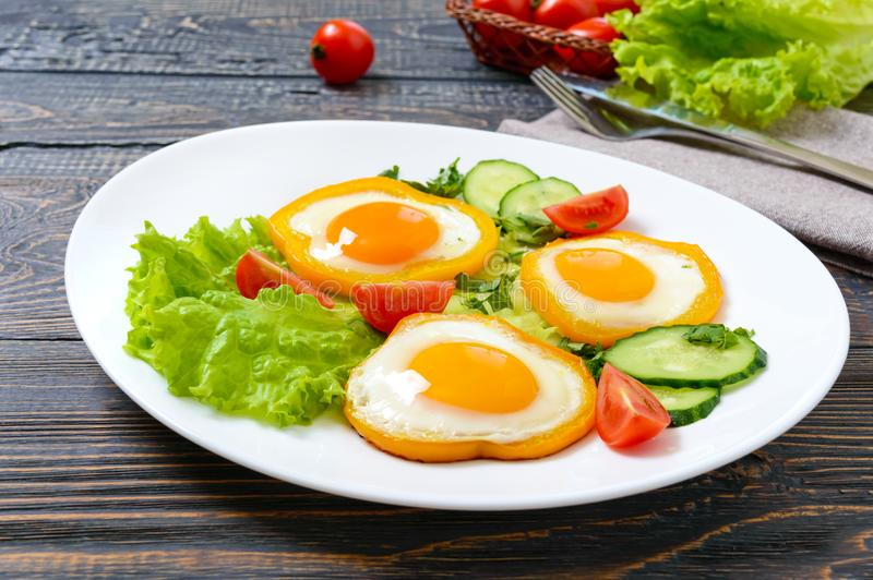 Fried egg in a circle of sweet pepper on a white plate with fresh vegetables on a wooden background. stock photo