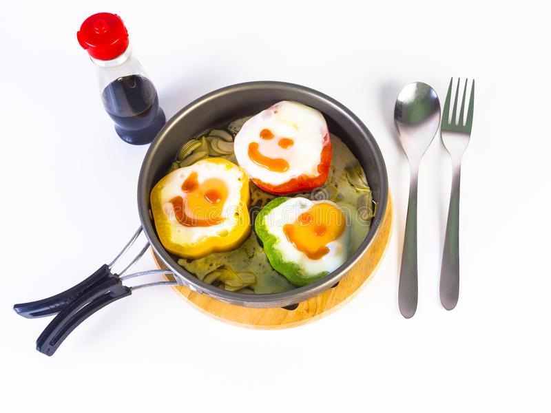 Fried egg on colorful peppers on pan. With spoon and fork royalty free stock photos