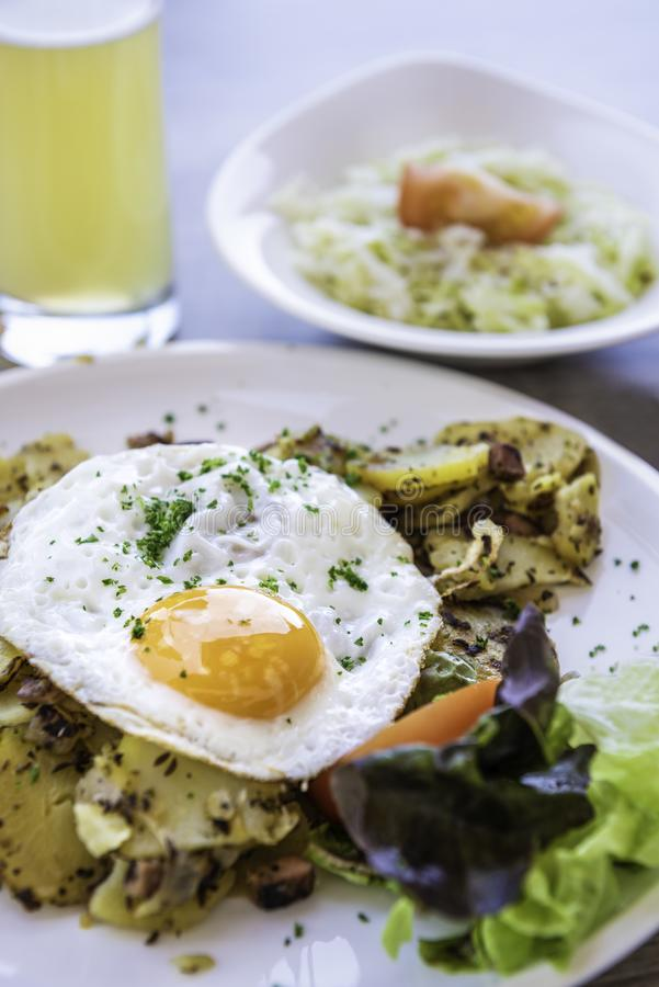 Fried egg with fried potatoes, ham, cabbage salad and beer. On white background stock photo