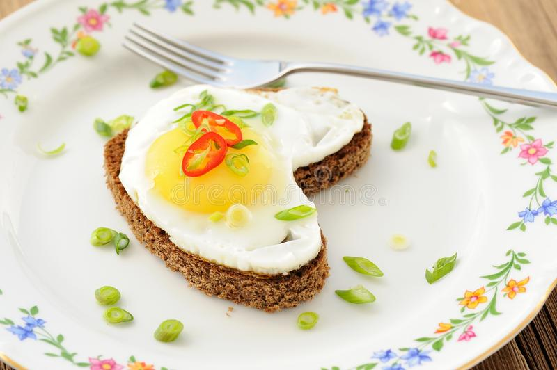 Fried egg heart rye sandwich with scallion, chili and fork on white plate side view royalty free stock photos