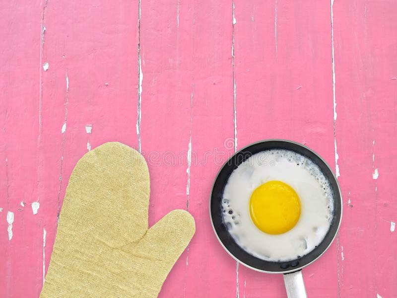 Fried egg in metal frying pan with silver steel handle and brown earth tone oven glove on pastel pink wood kitchen table. Preparation cooking breakfast, flat lay royalty free stock photos