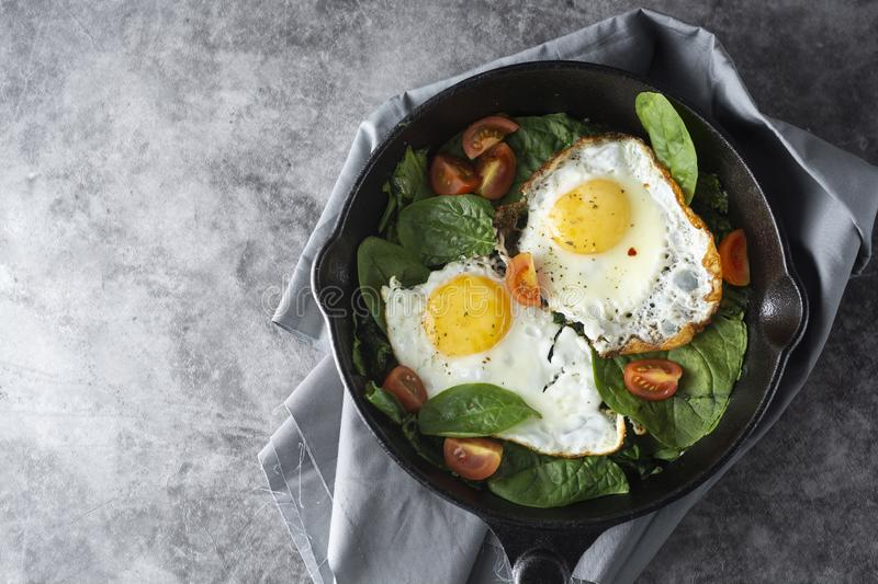 Fried egg on a pan served with fresh cherry tomatoes. Healthy breakfast. Fried egg on a pan served with fresh cherry tomatoes. Healthy food, dark, background royalty free stock photo