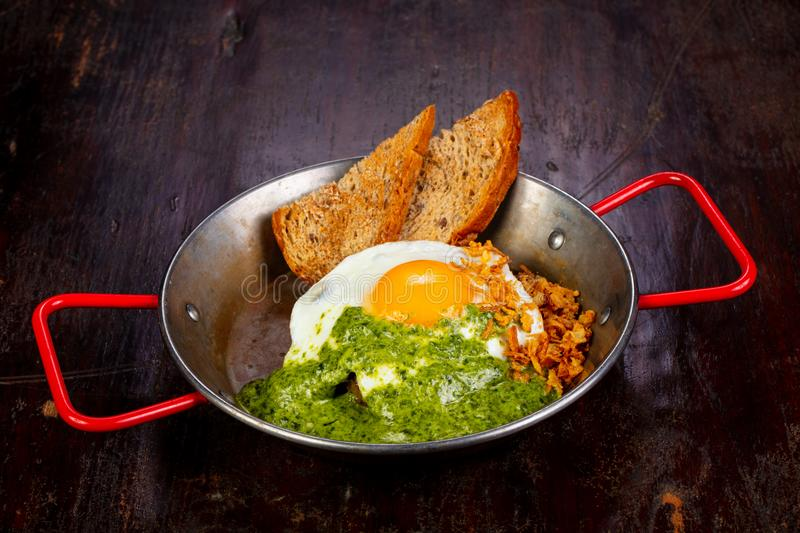 Fried egg with pesto. And bread royalty free stock images