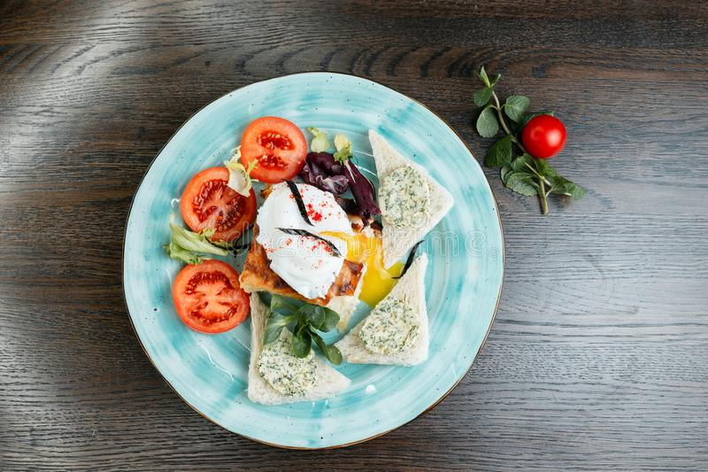 Egg `Poached ` with slices of fresh tomatoes and fried toasts with delicious pate and greens on a blue plate in a restaurant stock images