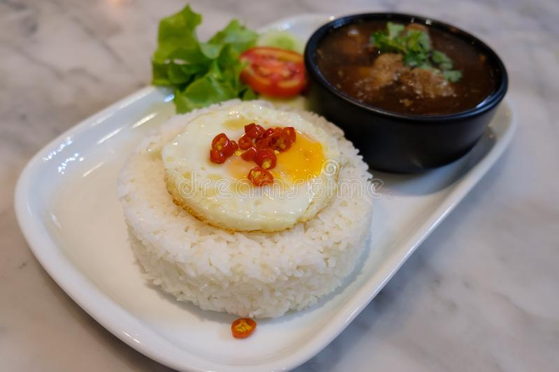 Fried egg on rice with boil soup. Fried egg on rice with boil soup on white tray on table stock image