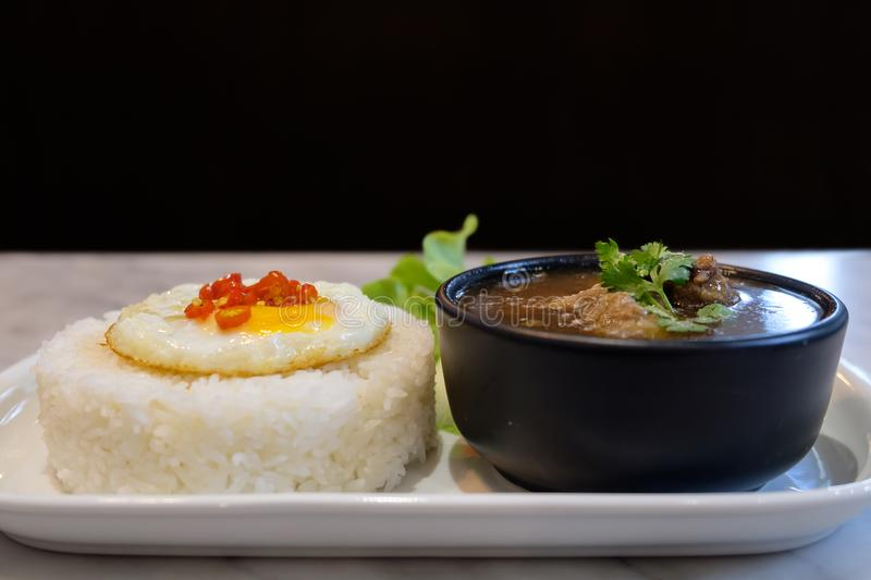 Fried egg on rice with boil soup. Fried egg on rice with boil soup on white tray on table on black background stock photography