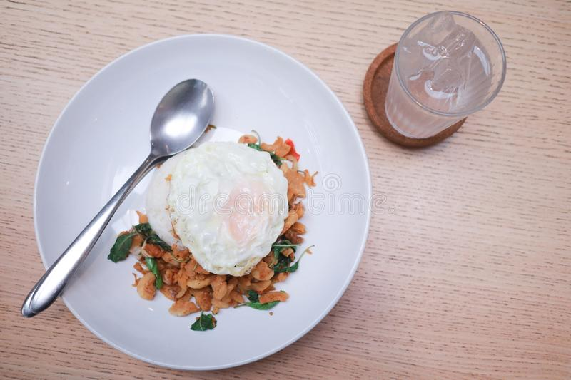 Fried egg on Rice topped with stir-fried pork and basil with water on the table royalty free stock photo
