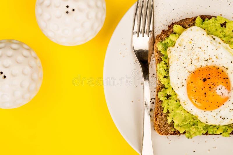 Fried Egg Sunny Side Up no fá aberto do abacate esmagado e do pão de Rye foto de stock royalty free