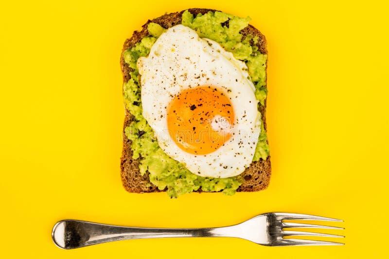 Fried Egg Sunny Side Up no fá aberto do abacate esmagado e do pão de Rye imagem de stock royalty free