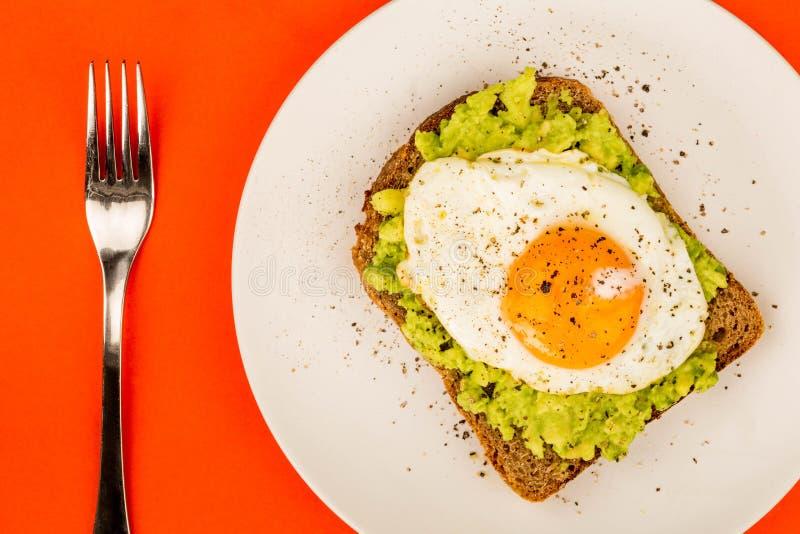 Fried Egg Sunny Side Up no fá aberto do abacate esmagado e do pão de Rye fotos de stock royalty free