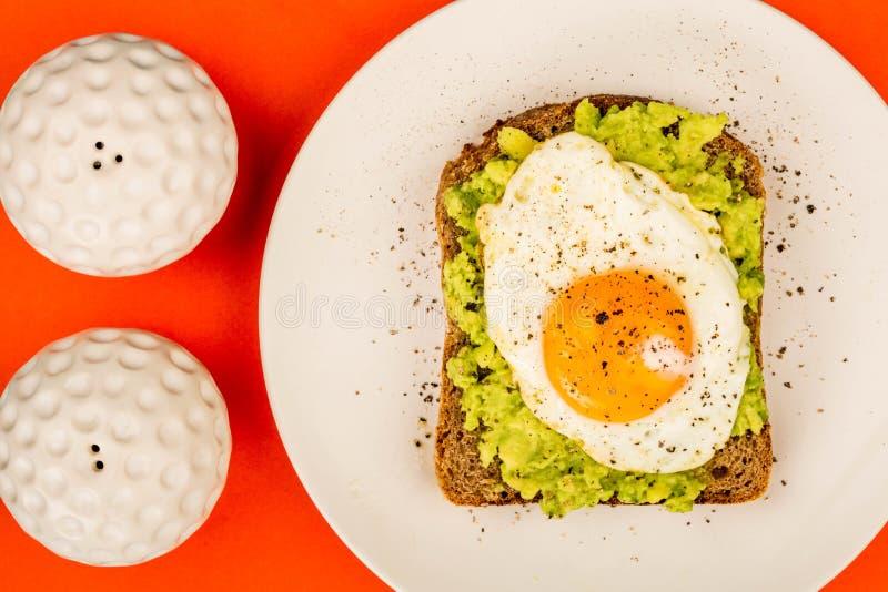 Fried Egg Sunny Side Up no fá aberto do abacate esmagado e do pão de Rye imagens de stock
