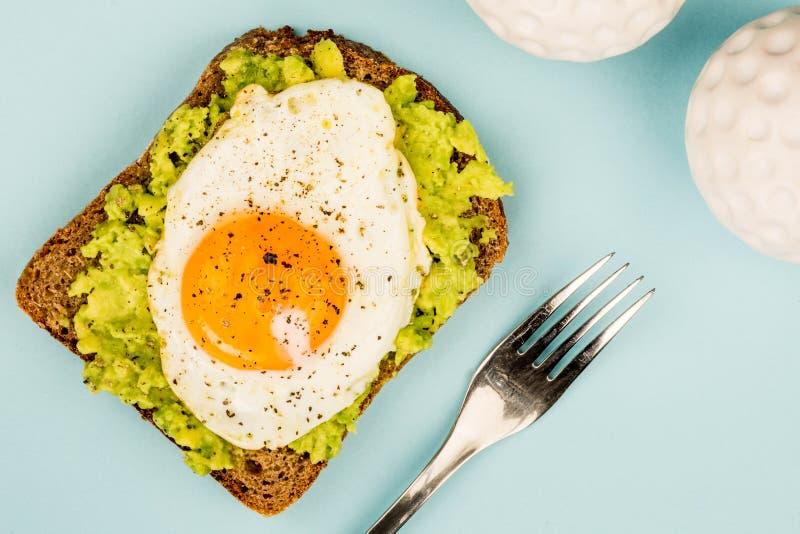 Fried Egg Sunny Side Up no fá aberto do abacate esmagado e do pão de Rye fotografia de stock royalty free