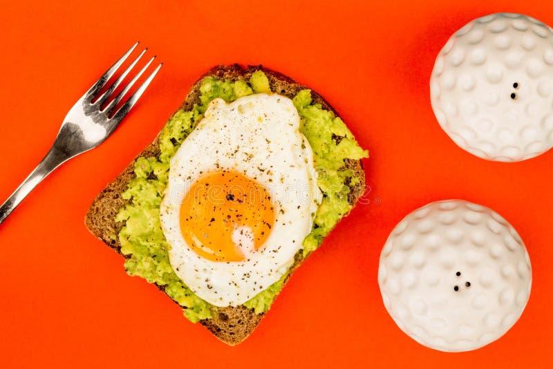 Fried Egg Sunny Side Up no fá aberto do abacate esmagado e do pão de Rye fotos de stock