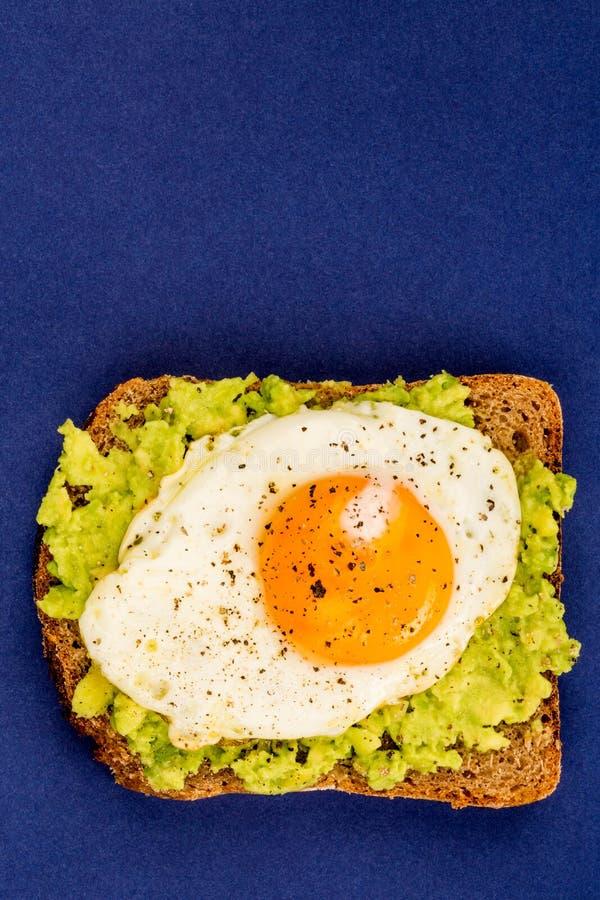 Fried Egg Sunny Side Up no fá aberto do abacate esmagado e do pão de Rye fotografia de stock