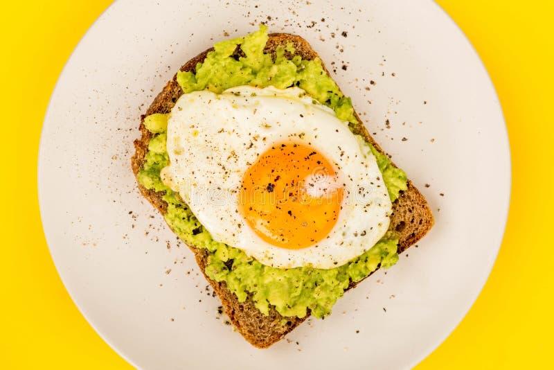 Fried Egg Sunny Side Up no fá aberto do abacate esmagado e do pão de Rye imagens de stock royalty free